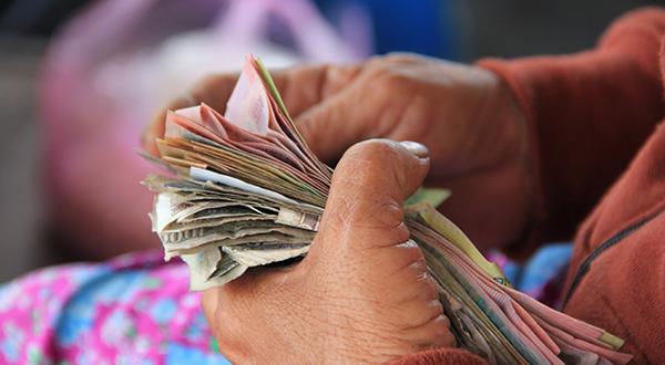 mãos segurando notas de dinheiro