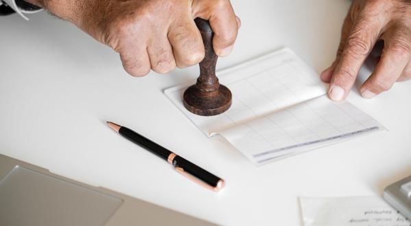 mão carimbando documento para autorizar pagamento